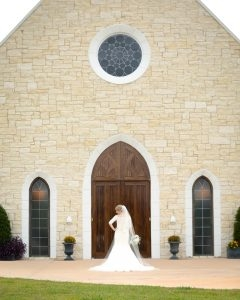 The bride shows off her dress and the architecture of the chapel
