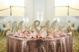 Glitter and sparkles mark the head table at this wedding reception