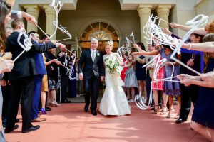 Ribbon wands point the happy couple to their exit