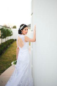 A beautiful bride poses outside the wedding venue