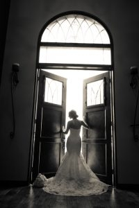 A fashionable bride poses before the venue doors