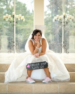 The bride carries a sign for her parents