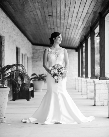 The bride poses for a portrait on a beautiful patio