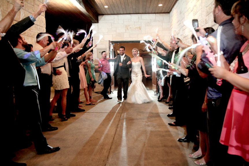 Glow sticks lead the bride and groom to their exit
