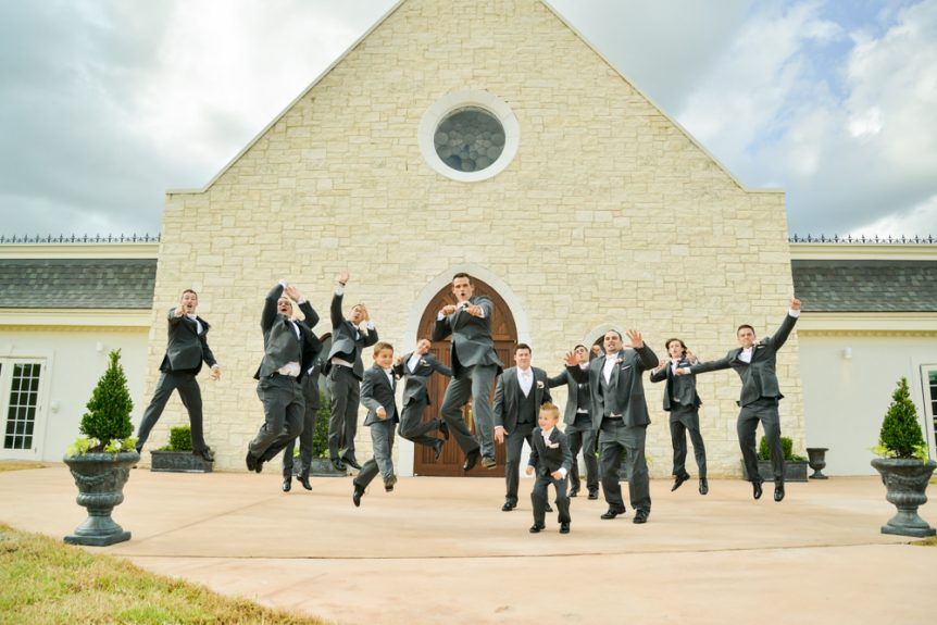 The groomsmen jump with joy in front of the wedding chapel