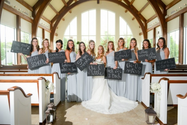 The bridesmaids hold signs to inform of how they met the bride