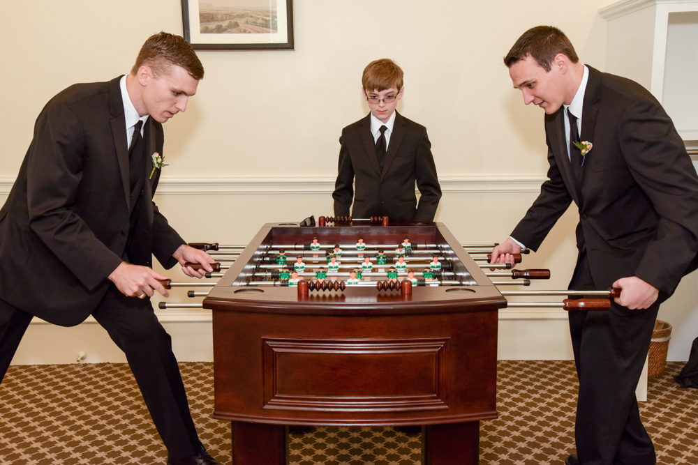 The groomsmen play foosball before the ceremony begins