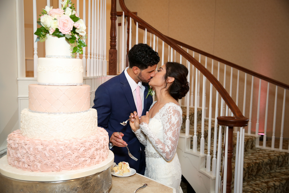 The newlyweds have a kiss after they share the first slice of cake