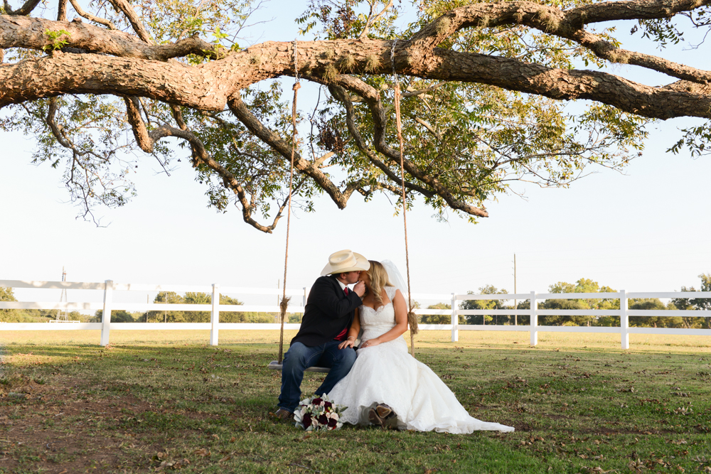 A cowboy and cowgirl take a swing and a kiss