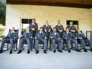 The groomsmen pose for a portrait in rocking chairs