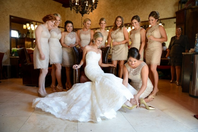 The Maid of Honor helps the bride put on her fabulous heels