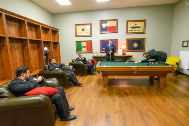 The groomsmen take a moment to play pool