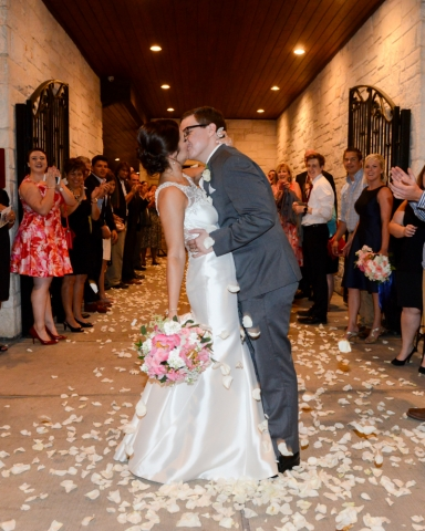 Excited guests throw petals at the happy couple as they exit