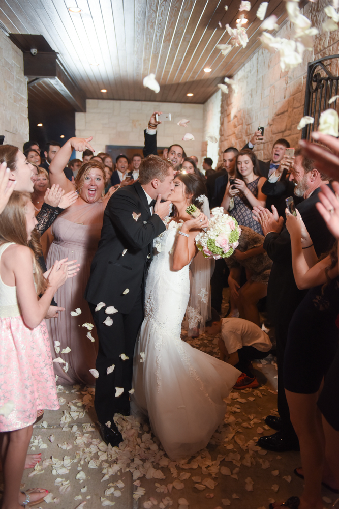 An exciting wedding exit sealed with a kiss