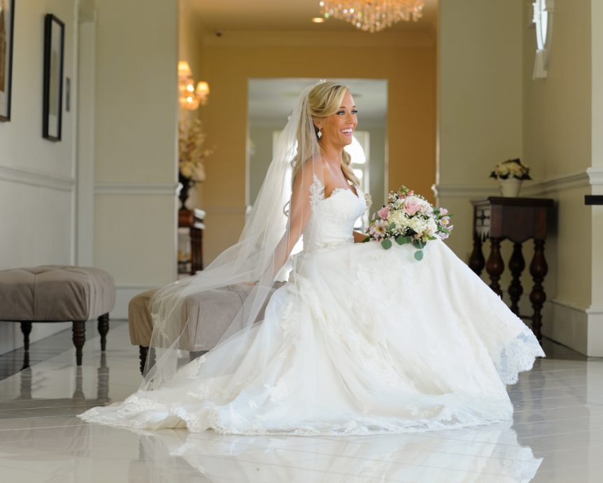 The bride poses for a portrait in her reception venue's hall