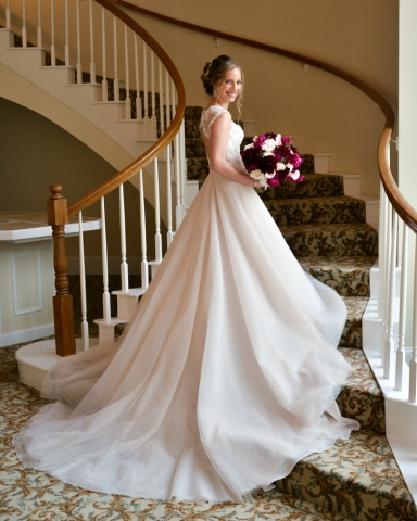 A bridal portrait on stairs show off the length of her train