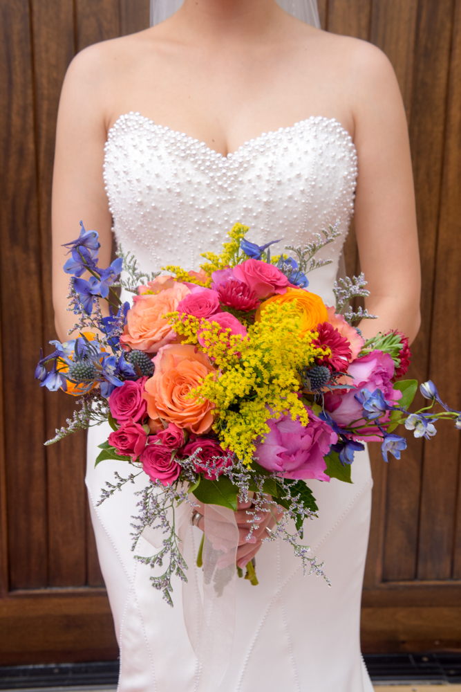 A beaming bride holds her colorful bouquet
