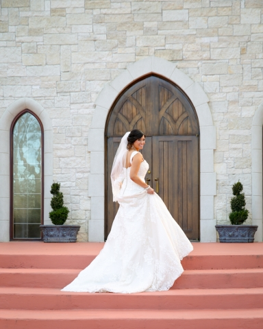 The bride poses in front of the chapel